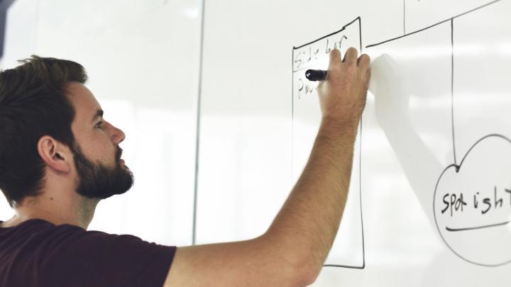 Man providing training on whiteboard.
