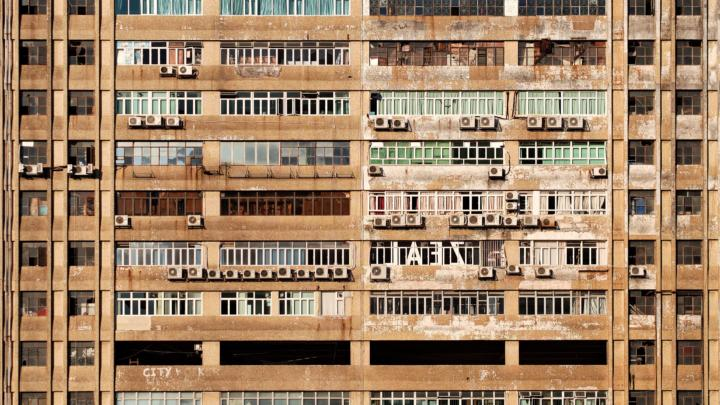 A dirty-looking and damaged large apartment building facade with a lot of air conditioning units outside windows