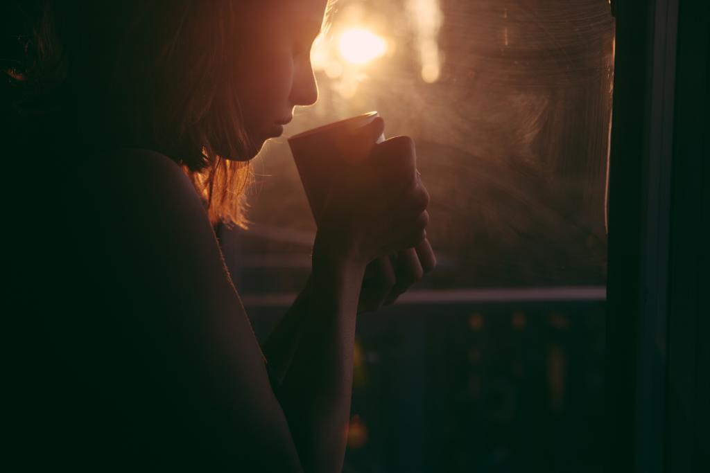A girl is drinking tea looking sad as sun goes down.