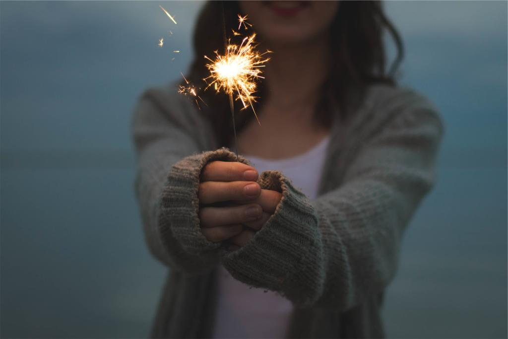 A girl holding a sparkler up in sign of hope.